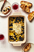 Baked feta cheese with olives in a baking dish