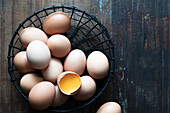 Whole eggs and a cracked egg in a wire basket