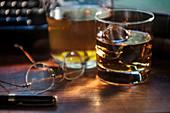 Whiskey glass and eyeglasses next to typewriter on desk