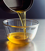 Pouring ghee from a pot into a glass bowl