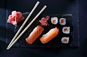 Nigiri sushi and hosomaki sushi rolls with fresh salmon fillet