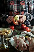 Frau schält Apfel für die Füllung von Hähnchen