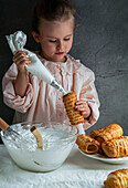 Little beautiful girl prepares puff rolls and fills them with cream