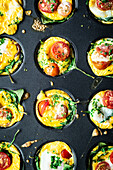 Baked egg muffins with spinach and tomatoes