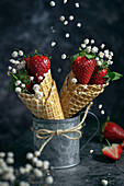 Strawberries with flowers in waffle cones