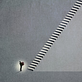 Man at the bottom of tall staircase, conceptual illustration