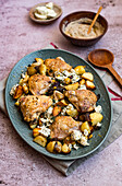Roast chicken thighs with potatoes, red onions, feta and Harissa