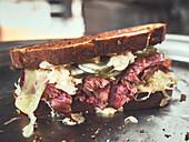 Reuben sandwich with corned beef, cheese, and sauerkraut