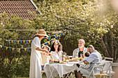 Family celebrating midsummer in the garden (Sweden)