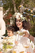 Young woman with flower wreath and little boy (summer solstice party, Sweden)