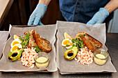 Kellnerhände halten frisch zubereitetes Essen