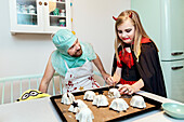 Father and daughter in Halloween costumes preparing food