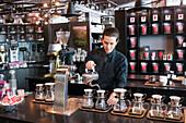Female barista preparing coffee at counter