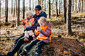 Father and daughters having picnic in forest