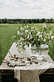 Tray with cheese, chutney and white wine and glass vase with blossom branches on garden table