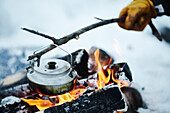 Kettle on stick over campfire