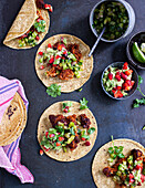 Tortillas with pulled jackfruit, strawberry guacamole and green tomato salsa