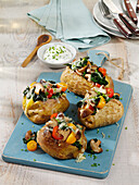 Baked potatoes filled with shiitake mushrooms, tomatoes, spinach and cheese