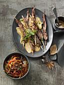 Lamb fillet skewers with saté sauce and vegetable salad