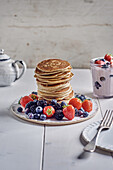 A stack of pancakes with fresh berries and strawberry yoghurt