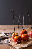 Candied apples on parchment paper on wooden table
