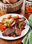 Beef brisket dinner with demi glace, roast potatoes and carrots