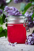 Lilac Syrup in a jar next to lilac blossom