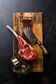 Raw fresh meat Tomahawk Steak, butcher cleaver and seasonings on wood board on dark background