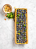 Rectangular blueberry tart with mint and almonds on a marble countertop