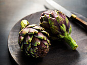 Two fresh artichokes on a wood tray and dark surface