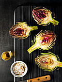 Fresh artichokes sliced in half ready on a black wood tray with oil and seasoning.