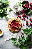 Summer berry galette on a white surface with greenery.
