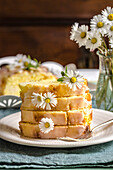 Lemon pound cake on a plate, on a table with daisies in a vase