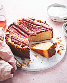 Rhubarb and Almond Cake with One Slice Resting on a Marble Board