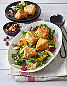 Fried cheese with pear, orange and lettuce salad