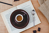 A cup of espresso on a book with a spoon and chocolate
