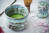 Matcha tea in tea bowl with matcha whisk and tea caddy