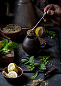 Latin American hot drink yerba mate in clay cup, herbs and lemon