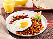 Mexican Chorizo hash topped with a fried egg and garnished with a wedge of orange