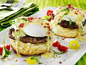 Blackened pork sausage patty Eggs Benedict with a poached egg and Hollandaise sauce on biscuits