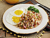Canadian Bacon hash and fried eggs with black pepper breakfast
