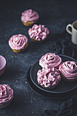 Cupcakes with pink frosting on a dark surface