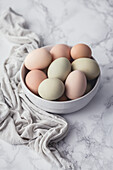 Fresh eggs in a bowl, on a marble surface