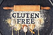 'Gluten free' Schriftzug in Mehl und Löffel mit verschiedene glutenfreien Mehlsorten