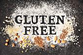 'Gluten free' Schriftzug in Mehl sowie glutenfreie Körner und Nüsse