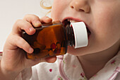 Young child putting a medicine bottle in his mouth