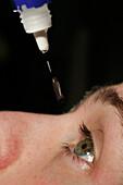 Young man applying eye drops