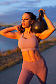 Young woman holding kettlebell on shoulder at riverbank
