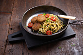 Spaghetti with falafel, pesto and grilled cocktail tomatoes