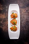 Chicken tikka (India) on a serving platter against a dark background